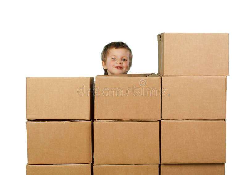 Petit garçon jetant un coup d'oeil par derrière les boîtes photo libre de droits