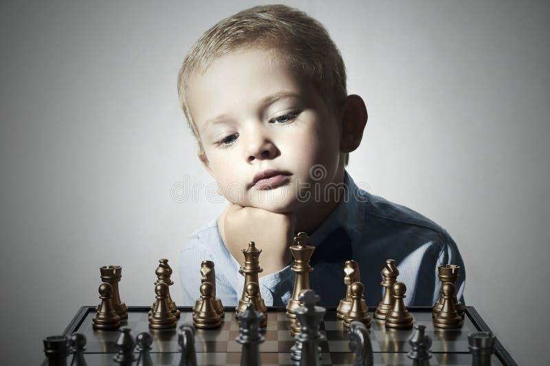 Petit garçon jouant aux échecs Gosse intelligent Petit enfant de génie Jeu intelligent Échiquier photographie stock