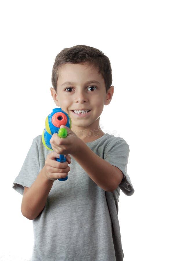Petit garçon jouant avec l'arme à feu d'eau en plastique photographie stock libre de droits