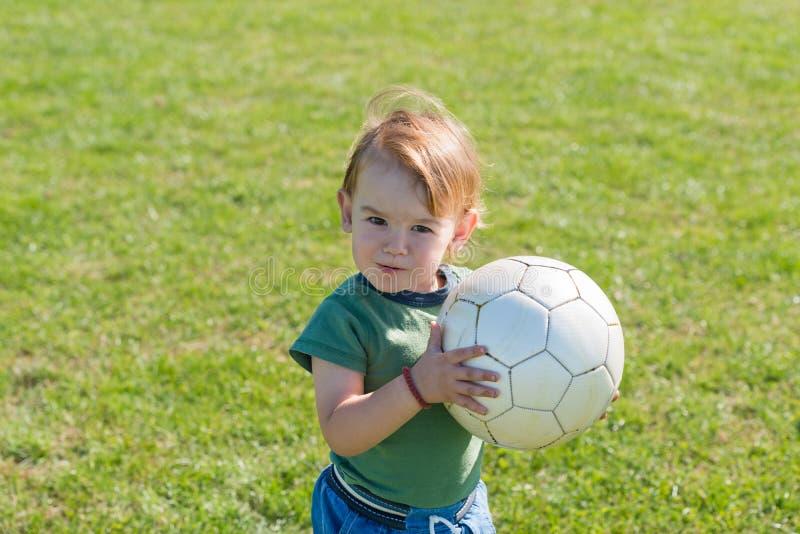 Petit garçon jouant avec la boule photos stock