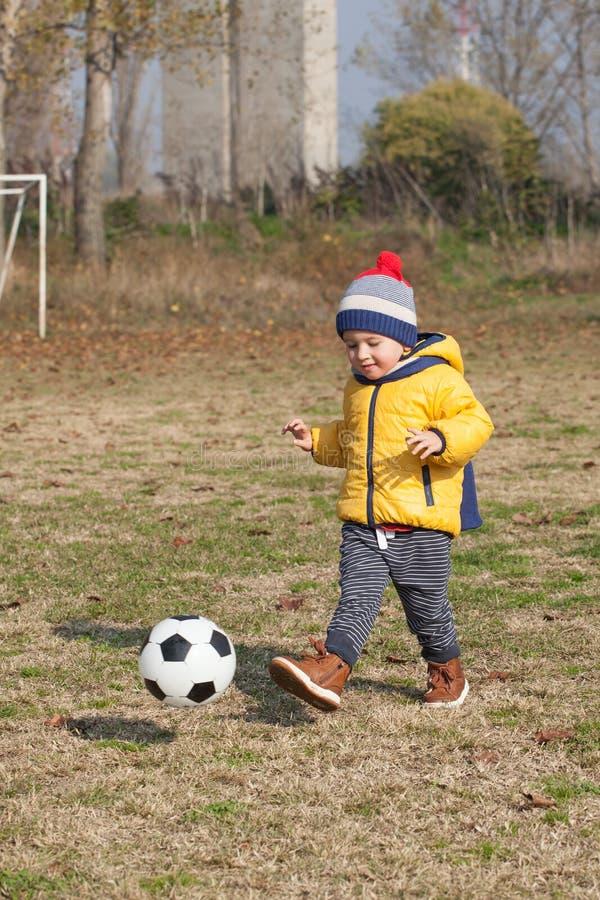 Petit garçon jouant avec la boule du football ou du football sports pour l'exercice et l'activité images libres de droits