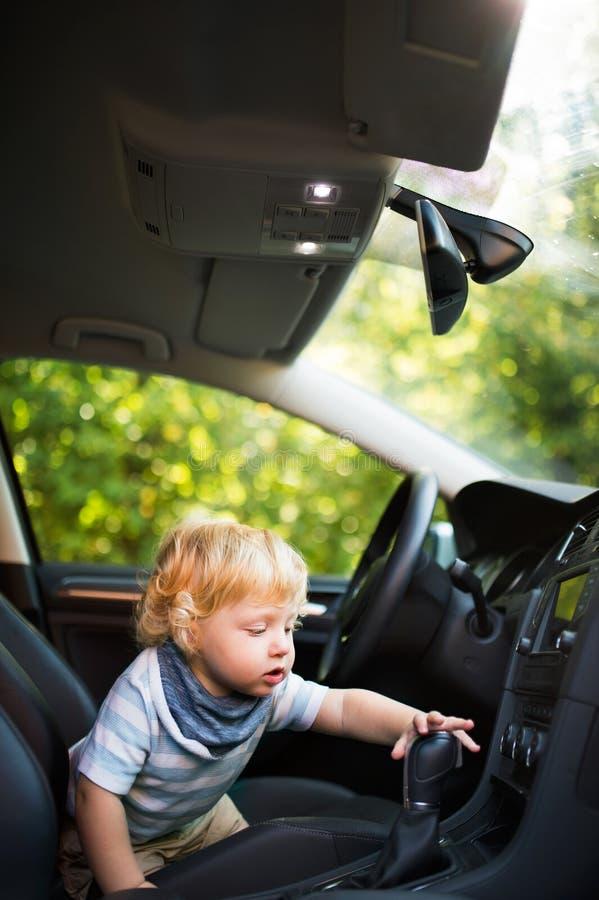 Petit garçon jouant dans la voiture, feignant pour la conduire photo stock