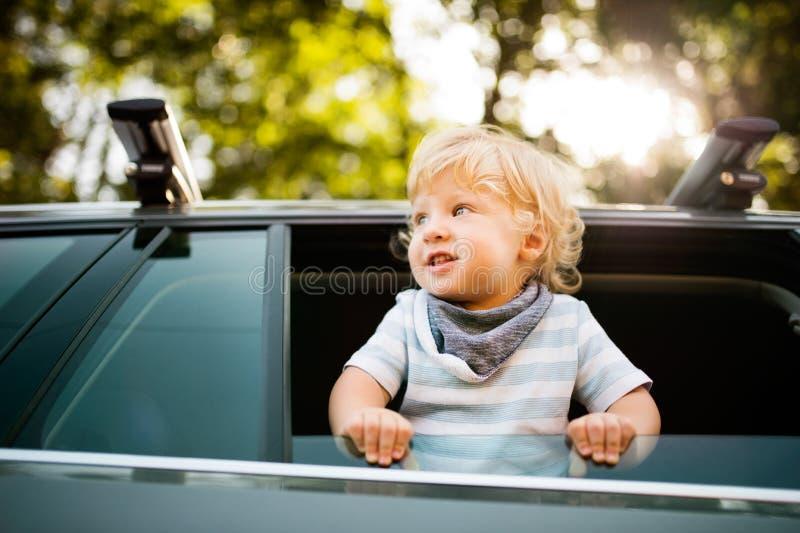 Petit garçon jouant dans la voiture, se penchant hors de la fenêtre photographie stock libre de droits