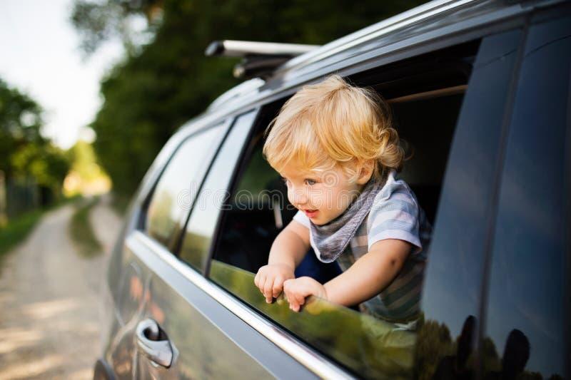 Petit garçon jouant dans la voiture, se penchant hors de la fenêtre photo stock