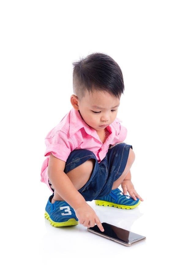 Petit garçon jouant des jeux au téléphone portable au-dessus du blanc photo stock