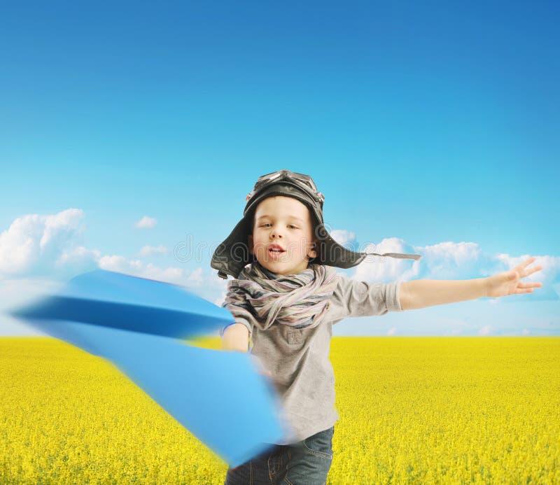 Petit garçon jouant l'avion de papier images stock