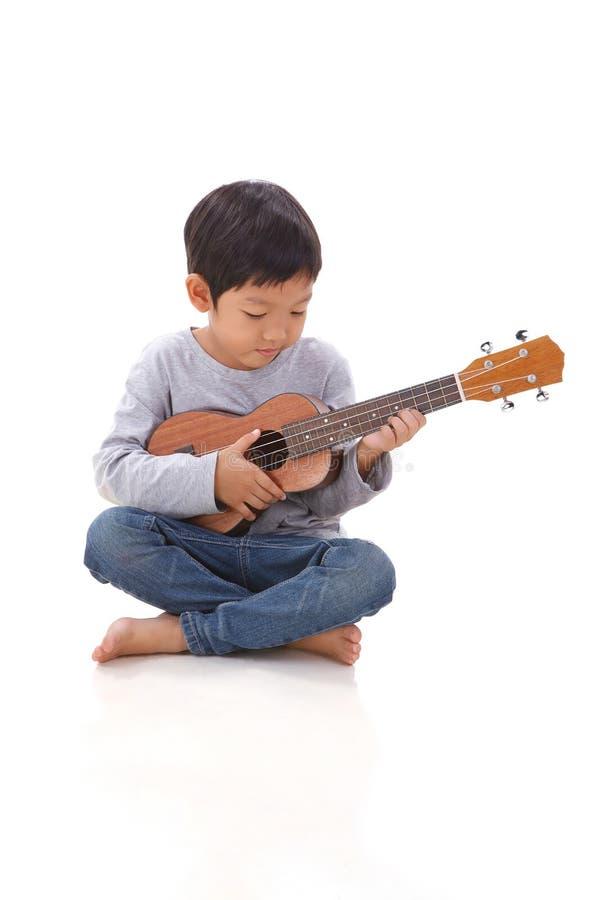 Petit garçon jouant l'ukulélé photo stock