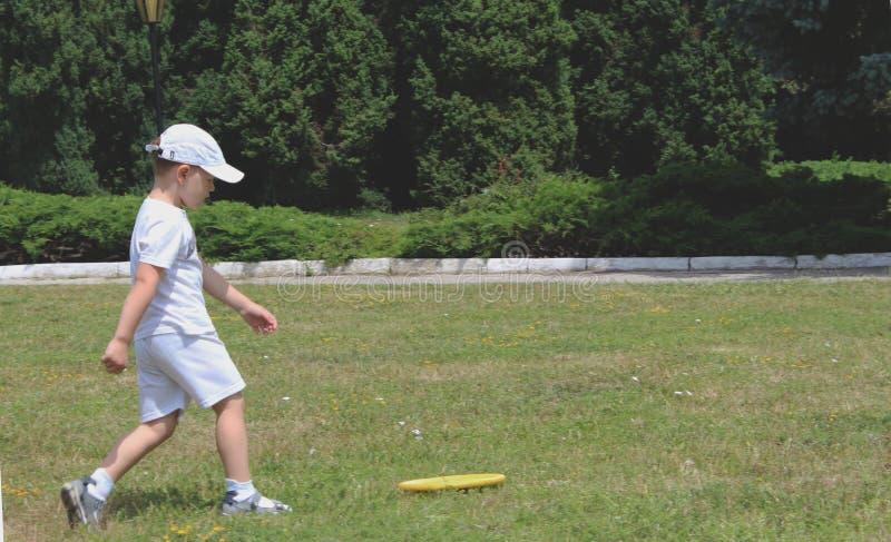 Petit garçon jouant le frisbee en parc images stock