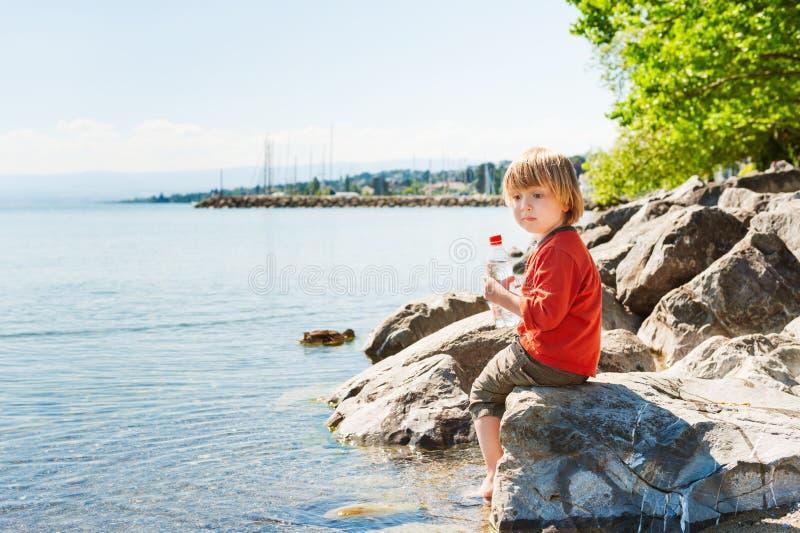 Petit garçon jouant par le lac photos libres de droits