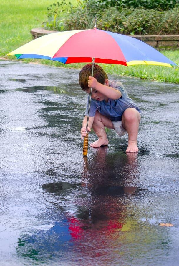 Petit garçon jouant sous la pluie photos libres de droits