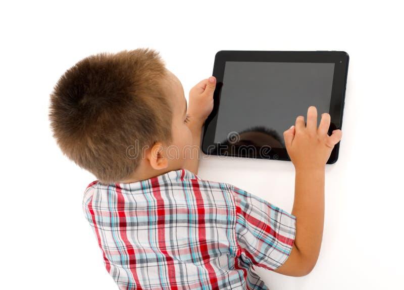 Petit garçon jouant sur la tablette image stock