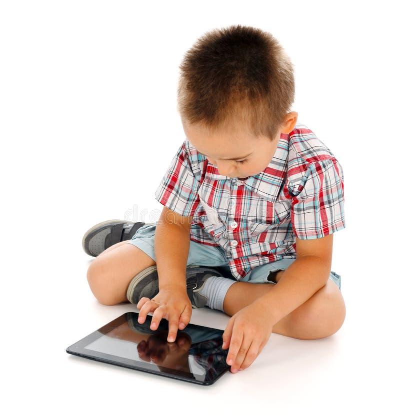 Petit garçon jouant sur le PC de comprimé images libres de droits