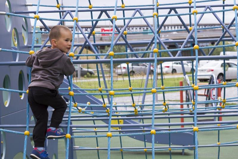 Petit garçon jouant sur le terrain de jeu en parc extérieur d'été photos libres de droits