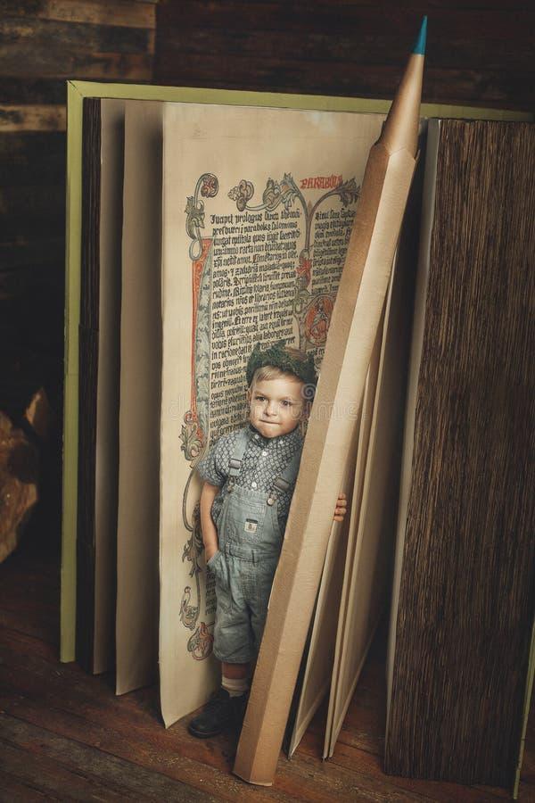Petit garçon lisant un livre, étude, symbole de la connaissance, bibliophile photo libre de droits