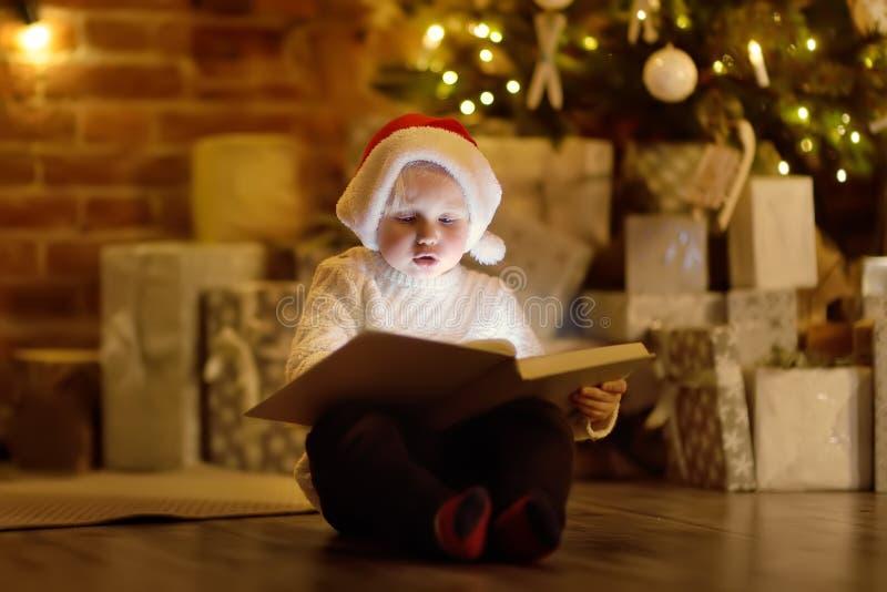 Petit garçon lisant un livre magique dans le salon confortable décoré photos stock