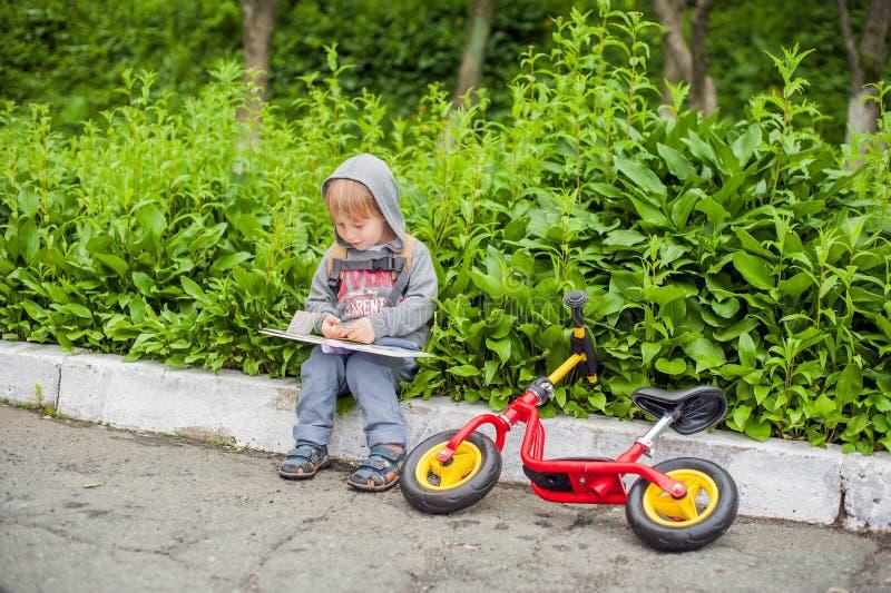 Petit garçon lisant un livre sous le grand arbre de tilleul photographie stock libre de droits