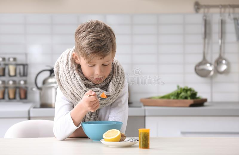 Petit garçon malade mangeant du bouillon pour traiter le froid à la table photo stock