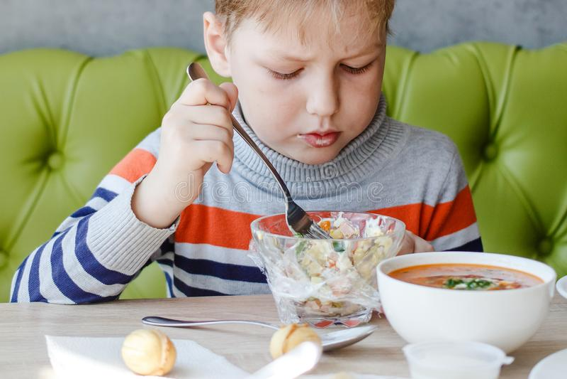 Petit garçon mangeant de la salade à la table photographie stock libre de droits