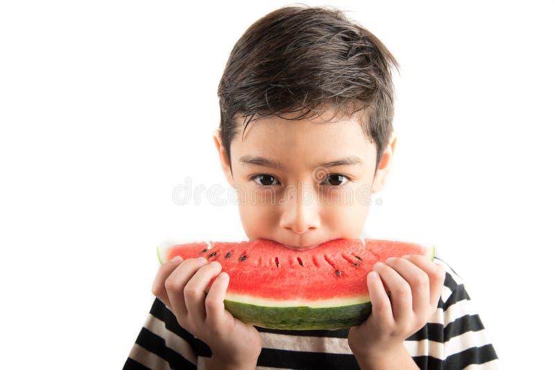 Petit garçon mangeant la pastèque l'heure d'été blanche de fond image libre de droits