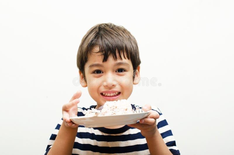 Petit garçon mangeant le visage heureux de riz images libres de droits