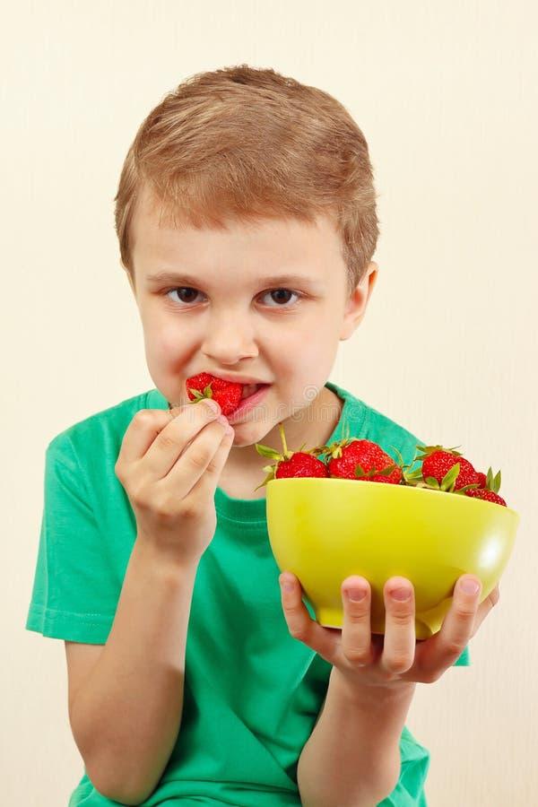 Petit garçon mangeant les fraises douces de la cuvette image stock