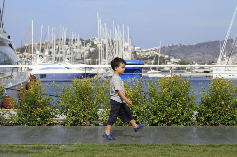 Petit garçon marchant dans une marina image stock