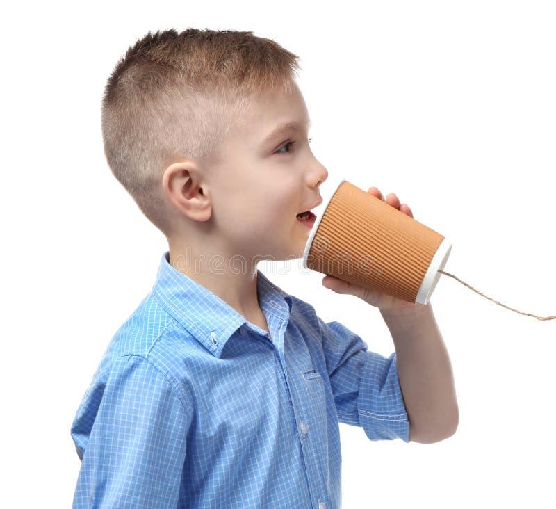 Petit garçon mignon à l'aide de la tasse en plastique comme téléphone images stock