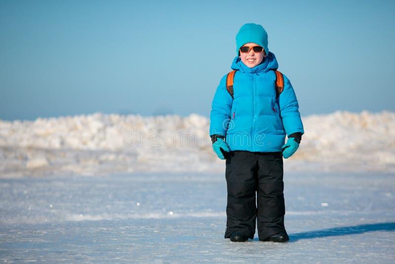 Petit garçon mignon à l'extérieur sur la plage de l'hiver photos stock