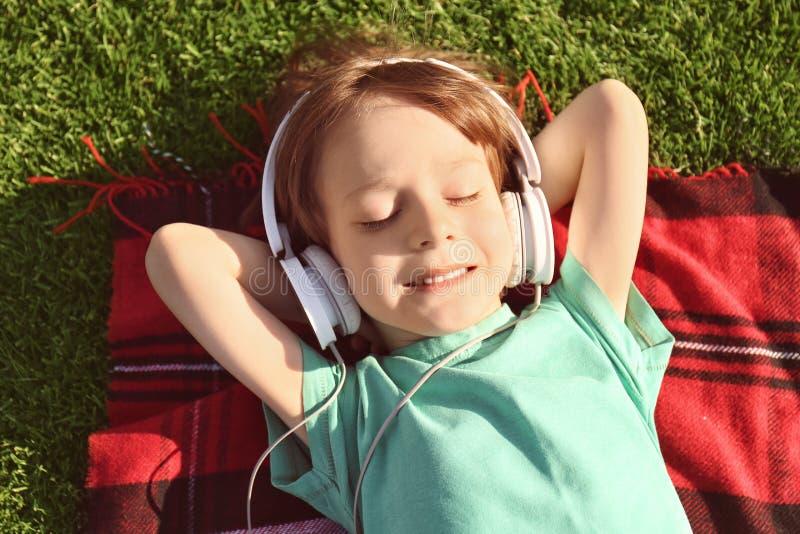 Petit garçon mignon écoutant la musique sur le plaid dehors photo stock