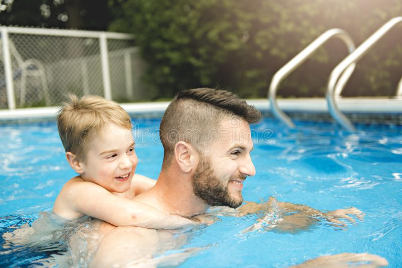 Petit garçon mignon apprenant à nager avec des parents dans la piscine images libres de droits
