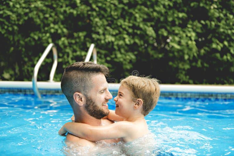 Petit garçon mignon apprenant à nager avec des parents dans la piscine photographie stock