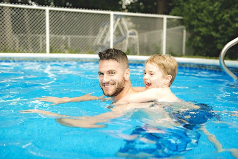 Petit garçon mignon apprenant à nager avec des parents dans la piscine photos libres de droits