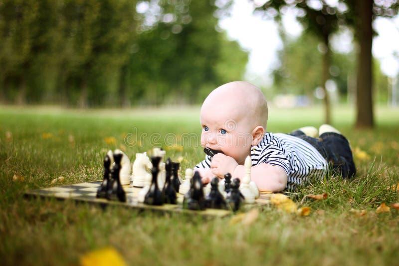 Petit garçon mignon avec des échecs en stationnement d'été photos libres de droits