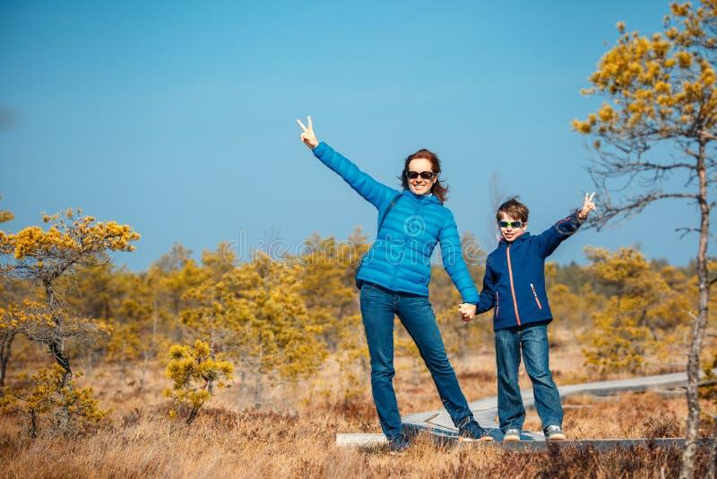 Petit garçon mignon avec la mère marchant sur la traînée dans le marais, parc national de Kemeri, Lettonie images libres de droits