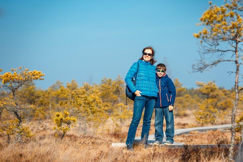 Petit garçon mignon avec la mère marchant sur la traînée dans le marais, parc national de Kemeri, Lettonie photo stock