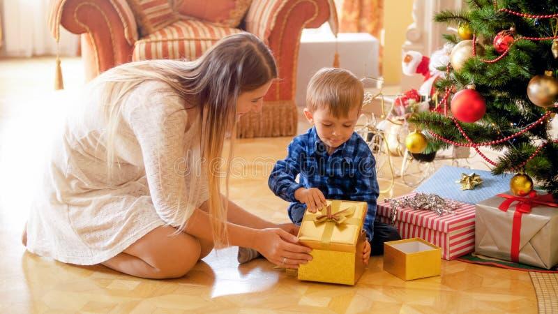Petit garçon mignon avec la mère s'asseyant sous l'arbre de Noël et le boîte-cadeau ouvert images libres de droits