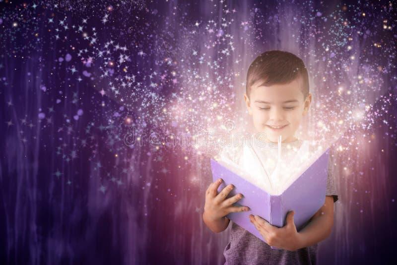 Petit garçon mignon avec le livre près du mur grunge images stock