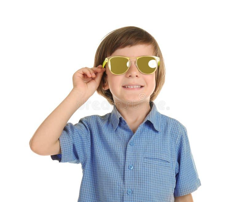 Petit garçon mignon avec les lunettes de soleil élégantes sur le fond blanc image stock