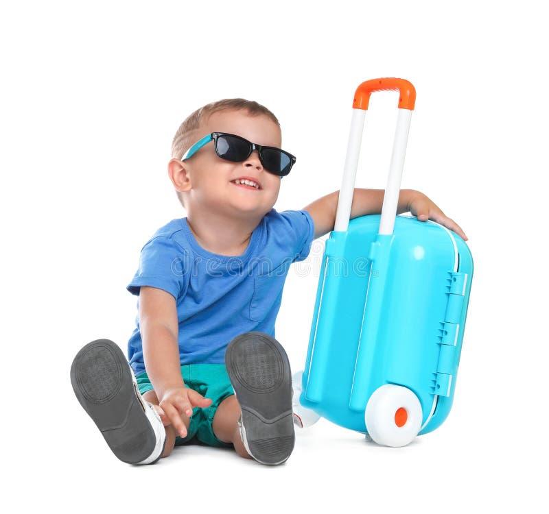 Petit garçon mignon avec les lunettes de soleil et la valise bleue images libres de droits