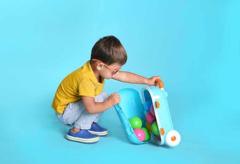 Petit garçon mignon avec les lunettes de soleil et la valise sur le fond bleu images libres de droits