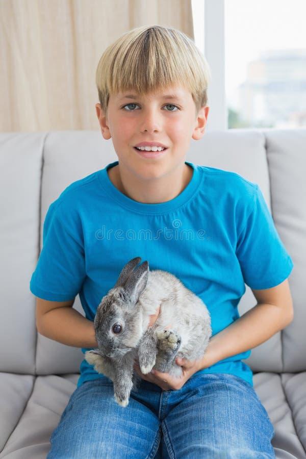 Petit garçon mignon avec son lapin d'animal familier photographie stock