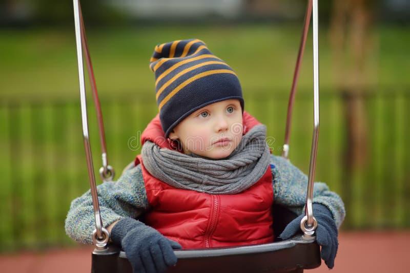 Petit garçon mignon ayant l'amusement sur le terrain de jeu extérieur Enfant sur l'oscillation photographie stock
