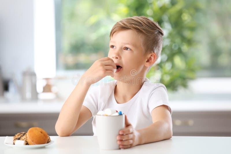 Petit garçon mignon buvant du cacao chaud et mangeant la guimauve à la table image libre de droits
