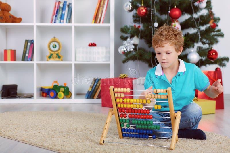 Petit garçon mignon comptant des cadeaux avec l'abaque en bois photo libre de droits