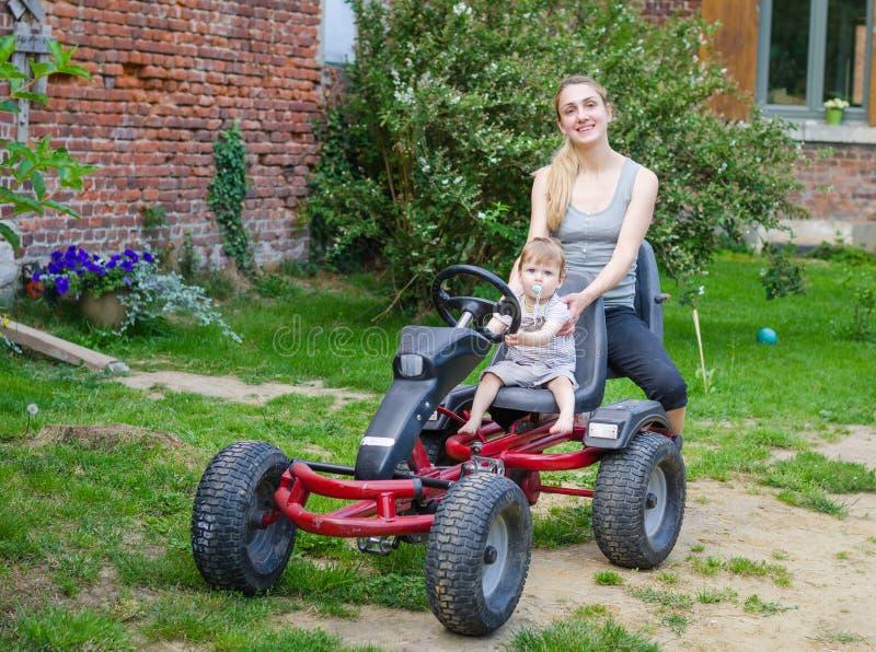 Petit garçon mignon conduisant la voiture de pédale avec la jeune mère photographie stock libre de droits