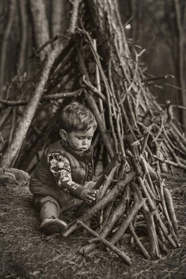 Petit garçon mignon construisant une hutte en bois images libres de droits