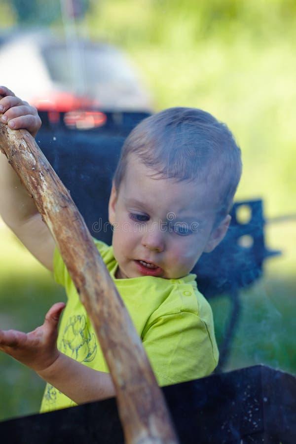 Petit garçon mignon coupant l'inflammation pour commencer un feu utilisant un bâton se concentrant soigneusement sur ce qu'il fai photographie stock