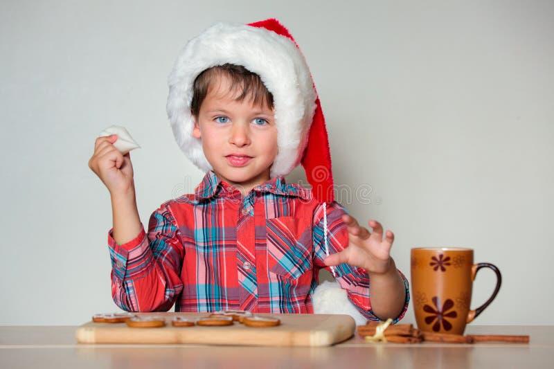 Petit garçon mignon décorant les biscuits de pain d'épice photo libre de droits