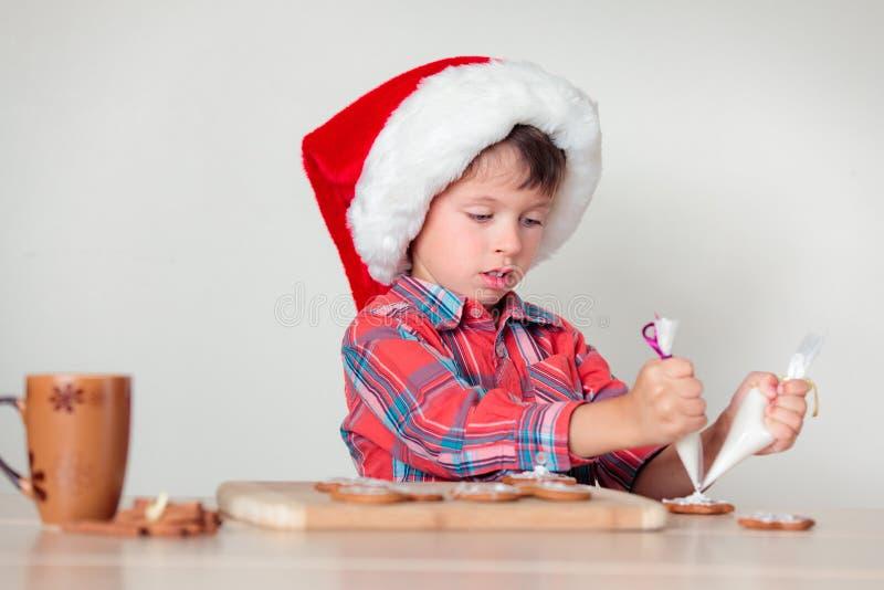 Petit garçon mignon décorant les biscuits de pain d'épice photographie stock