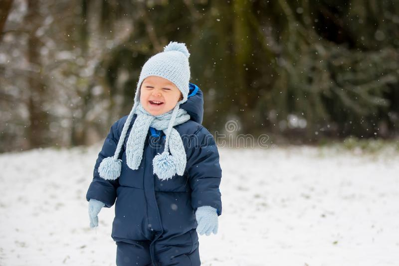 Petit garçon mignon d'enfant en bas âge, jouant dehors avec la neige un jour d'hiver image libre de droits